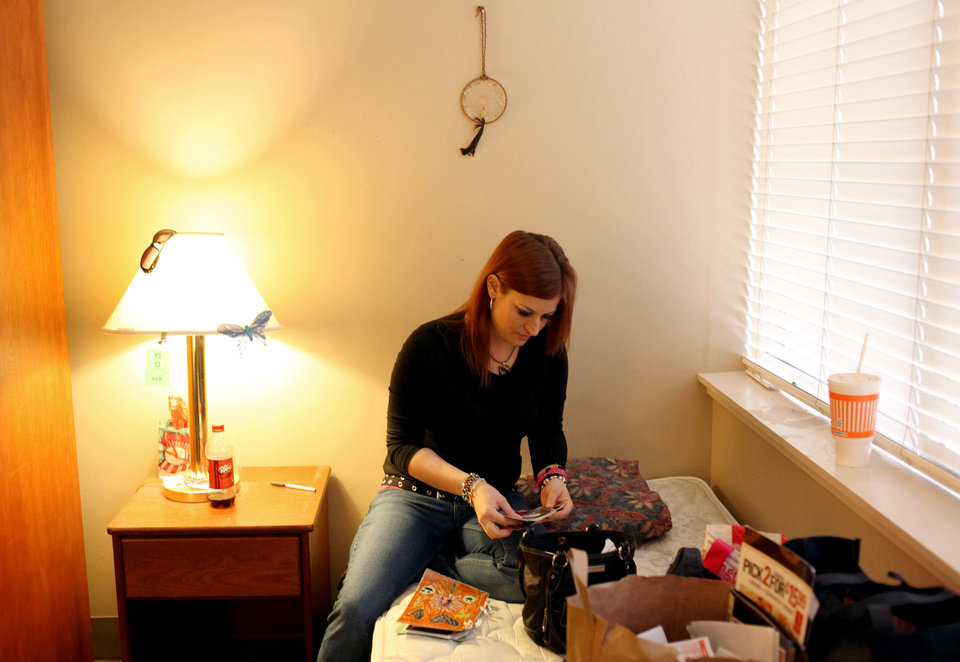Lindsay Arias sorts through pictures and mementos as she moves out of one room at 12&12 Inc. and into a new room and a new program at the same facility.