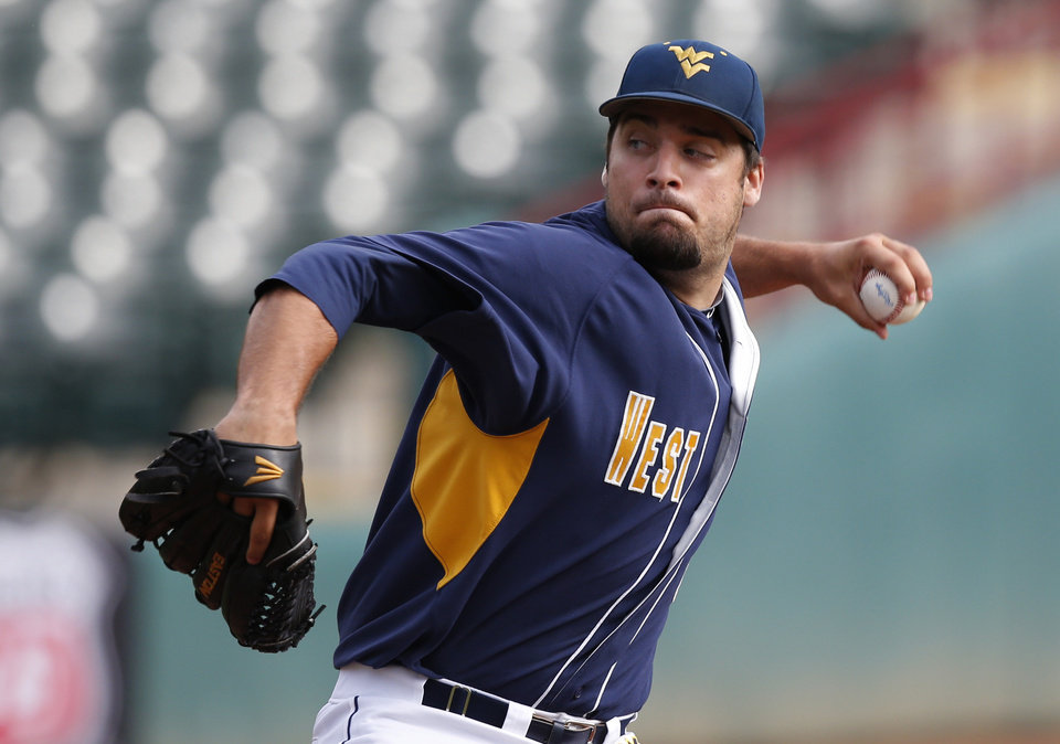 Photo - West Virginia's Harrison Musgrave pitches in the second inning of a first-round game against Kansas in the Big 12 conference baseball tournament in Oklahoma City, Wednesday, May 21, 2014. (AP Photo/Sue Ogrocki)