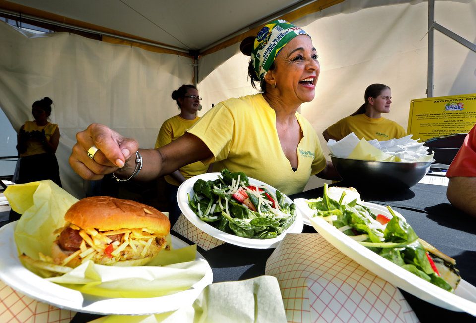 Photo -  Ana Davis from Cafe Do Brasil shows dishes at the Festival of the Arts at OKC's Bicentennial Park on Tuesday in Oklahoma City. [Photo by Steve Sisney, The Oklahoman]