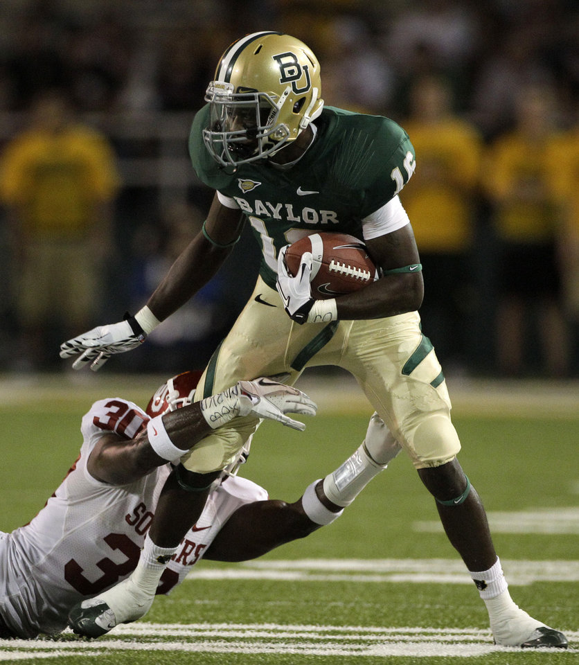 Baylor wide receiver Tevin Reese (16) breaks a tackle-attempt by Oklahoma defensive back Javon Harris (30) in the first half of an NCAA college football game on Saturday, Nov. 19, 2011, in Waco, Texas. (AP Photo/Tony Gutierrez)