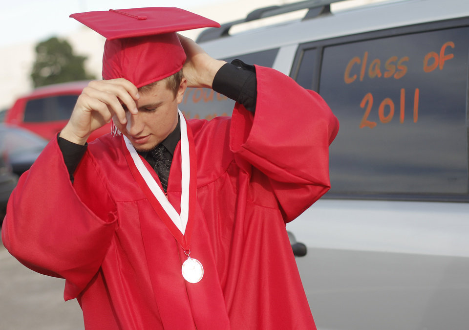 Blake Teter adjusts his cap before the Yukon High School Class of 2011 graduation at Oklahoma State Fair Park Arena, May 26, 2011. Photo by Doug Hoke, The Oklahoman.