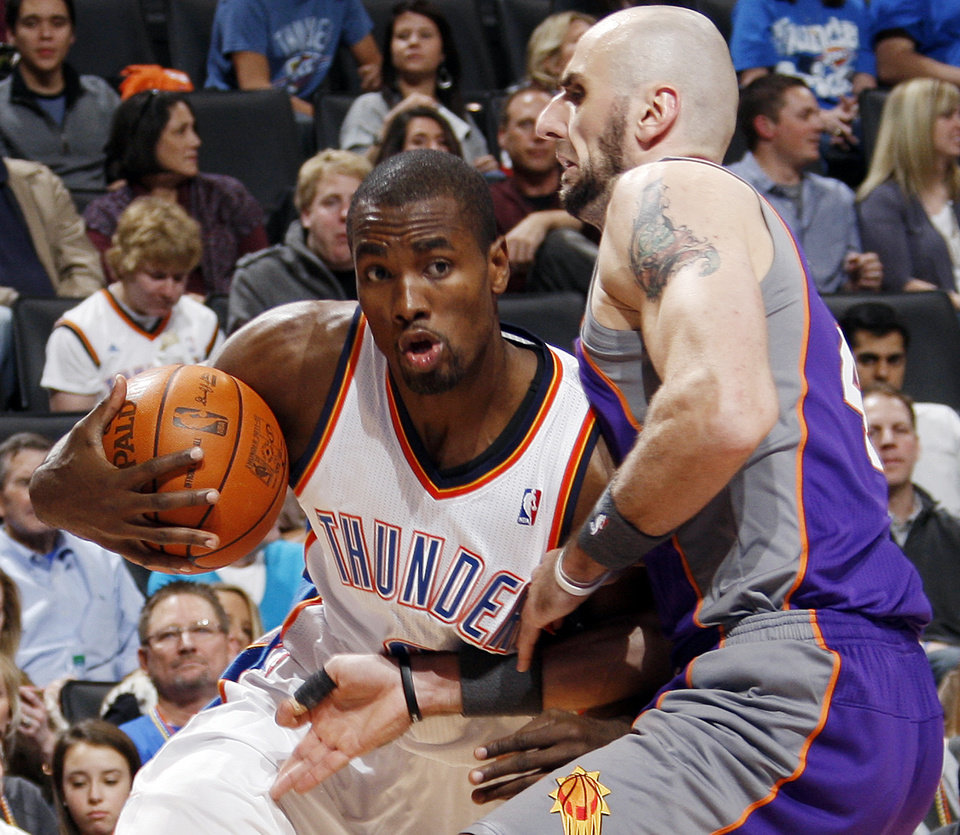 Photo - Oklahoma City's Serge Ibaka (9) tries to get the ball past Marcin Gortat (4) of Phoenix during the NBA basketball game between the Oklahoma City Thunder and Phoenix Suns at Chesapeake Energy Arena in Oklahoma City, Saturday, Dec. 31, 2011. Oklahoma City won, 107-97. Photo by Nate Billings, The Oklahoman
