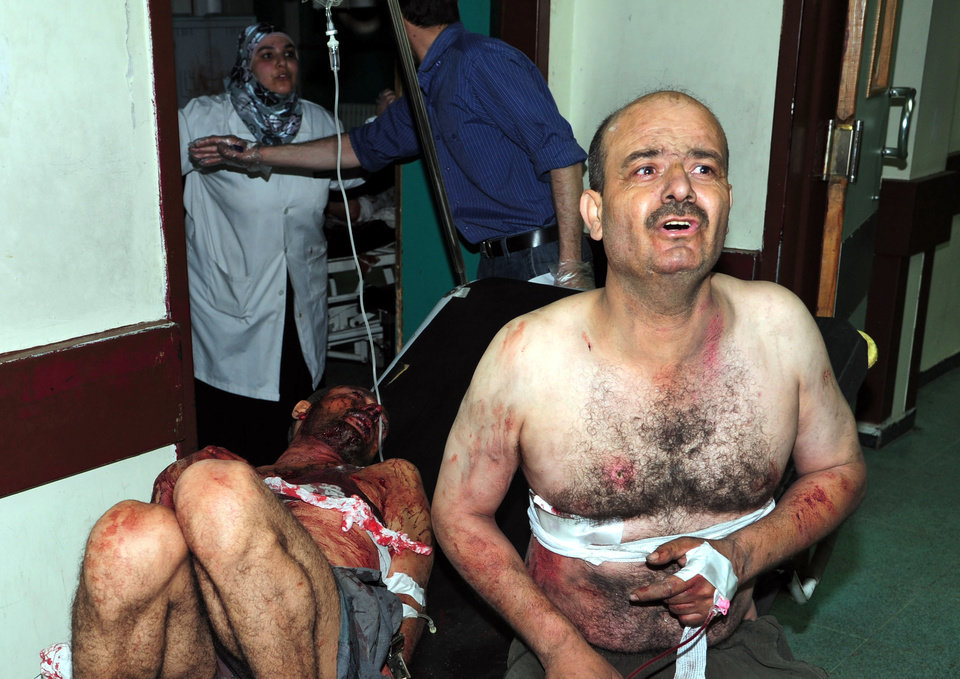 Photo - In this photo released by the Syrian official news agency SANA, two injured Syrian men who were wounded after two bombs exploded at Qazaz neighborhood, react at a hospital in Damascus, Syria, on Thursday May 10, 2012. Two strong explosions ripped through the Syrian capital Thursday, killing or wounding dozens of people and leaving scenes of carnage in the streets in an assault against a center of government power. (AP Photo/SANA) ORG XMIT: BEI110