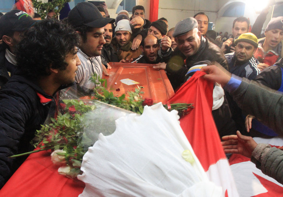 Photo - Relatives of slain opposition leader Chokri Belaid leave the house of his father while carrying the coffin prior to his funeral in Tunis, Friday, Feb. 8, 2013. Tunisia braced for clashes on Friday, with the capital shut down by a general strike and the army deployed for the funeral of a slain opposition leader expected to draw tens of thousands of mourners, and potentially many more. (AP Photo/Amine Landoulsi)