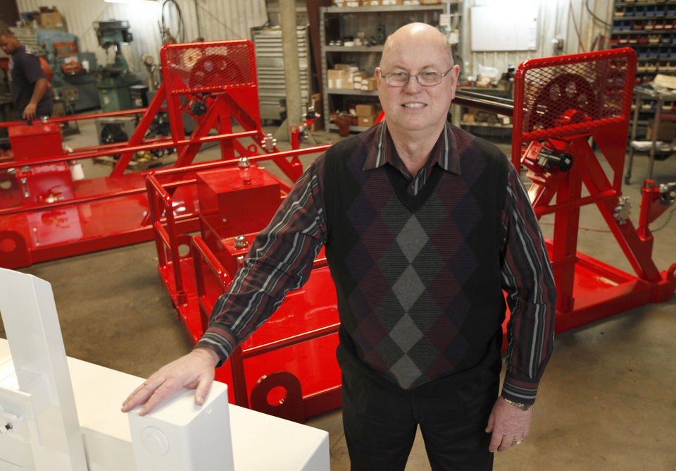 Darrell Scott, founder and president of Pro-Formance Mfg., poses in front of two skid-mounted industrial spooling trailers. Photo by Paul Hellstern, The Oklahoman <strong>PAUL HELLSTERN</strong>