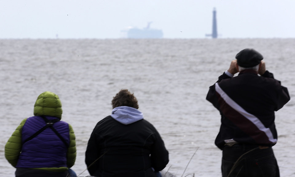 Photo - Residents sit on the shore and watch as the cruise ship Carnival Triumph is visible near Dauphin Island, Ala., Thursday, Feb. 14, 2013. The ship with over 1,000 passengers aboard has been idled for nearly a week in the Gulf of Mexico following an engine room fire. (AP Photo/Dave Martin)
