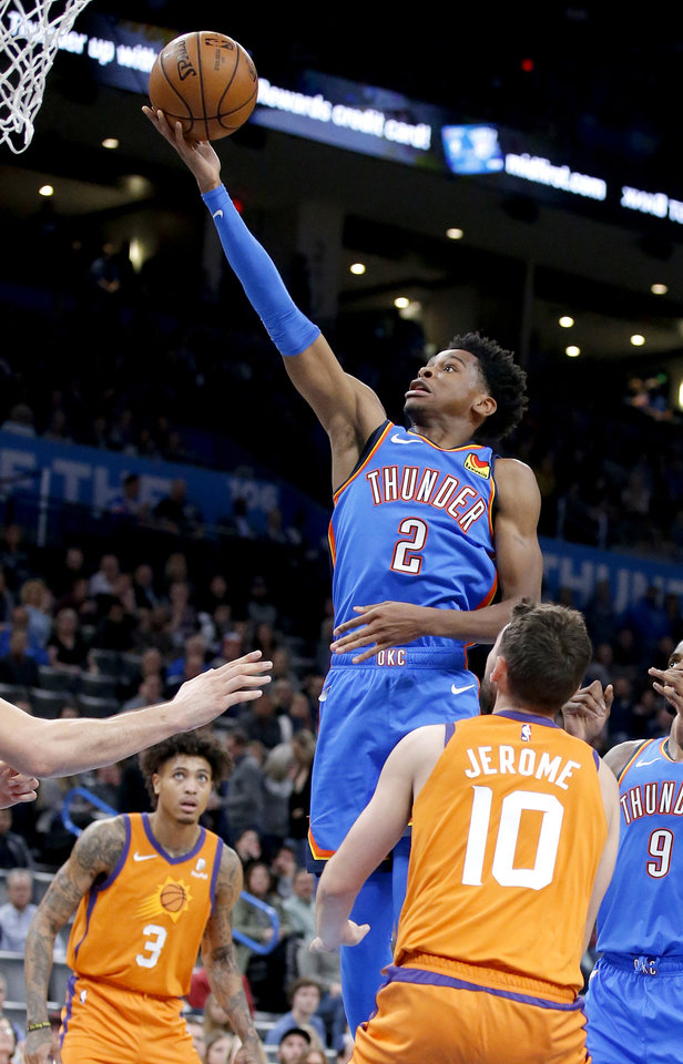 Photo - Oklahoma City's Shai Gilgeous-Alexander (2) goes up for a lay up in between Phoenix's Elie Okobo (2) and Phoenix's Ty Jerome (10) during the NBA basketball game between the Oklahoma City Thunder and the Phoenix Suns at the Chesapeake Energy Arena in Oklahoma City , Friday, Dec. 20, 2019.   [Sarah Phipps/The Oklahoman]