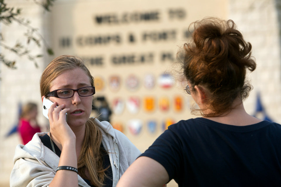 Photo - Krystina Cassidy, left, and Dianna Simpson attempt to make contact with their husbands who are stationed inside Fort Hood while standing outside of the Bernie Beck Gate on Wednesday, April 2, 2014, in Fort Hood, Texas. At least one person was killed and 14 injured in the shooting, and officials at the base said the shooter is believed to be dead. (AP Photo/ Tamir Kalifa)