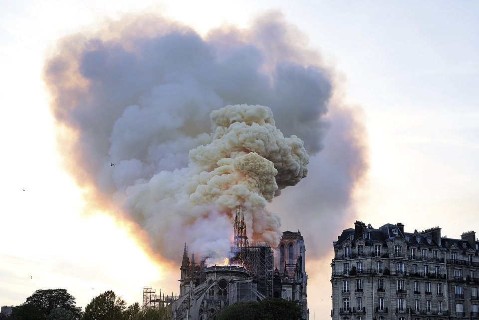 Photo - Flames and smoke rise as the spire on Notre Dame cathedral collapses in Paris, Monday, April 15, 2019. Massive plumes of yellow brown smoke is filling the air above Notre Dame Cathedral and ash is falling on tourists and others around the island that marks the center of Paris. (AP Photo/Diana Ayanna)