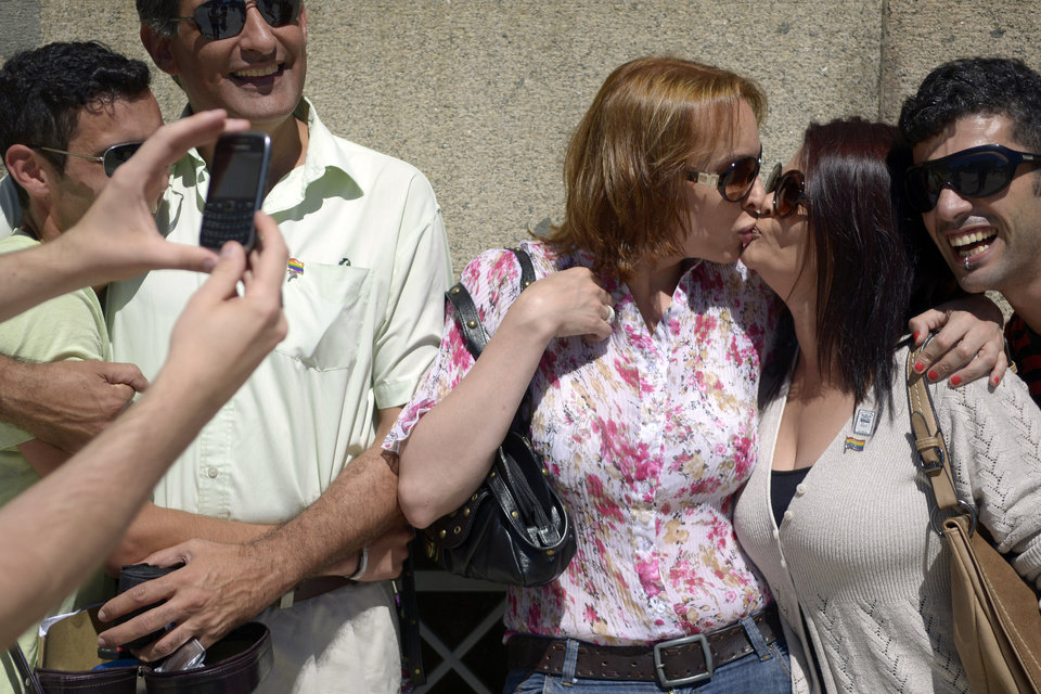 Gay couples pose for photos as they wait outside Parliament where same a sex marriage law is being debated in Montevideo, Uruguay, Tuesday, Dec. 11, 2012. Taboo-breaking Uruguay is poised to legalize gay marriage, with lawmakers debating Tuesday whether to create a single law governing marriage for heterosexuals and homosexuals.  The new proposal would make Uruguay the second nation in Latin America and the 12th in the world to legalize gay marriage, after The Netherlands, Belgium, Spain, Canada, South Africa, Norway, Sweden, Portugal, Iceland, Argentina and Denmark. (AP Photo/Matilde Campodonico)