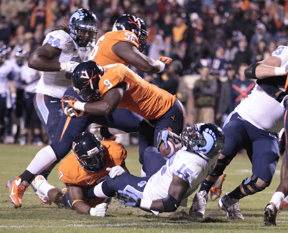 Photo -   North Carolina running back A.J. Blue (15) backs in for a touchdown as Virginia defensive end Eli Harold (7) and linebacker LaRoy Reynolds (9) try to make the stop during the first half of an NCAA college football game at Scott stadium Thursday, Nov. 15, 2012 in Charlottesville, VA (AP Photo/Steve Helber)