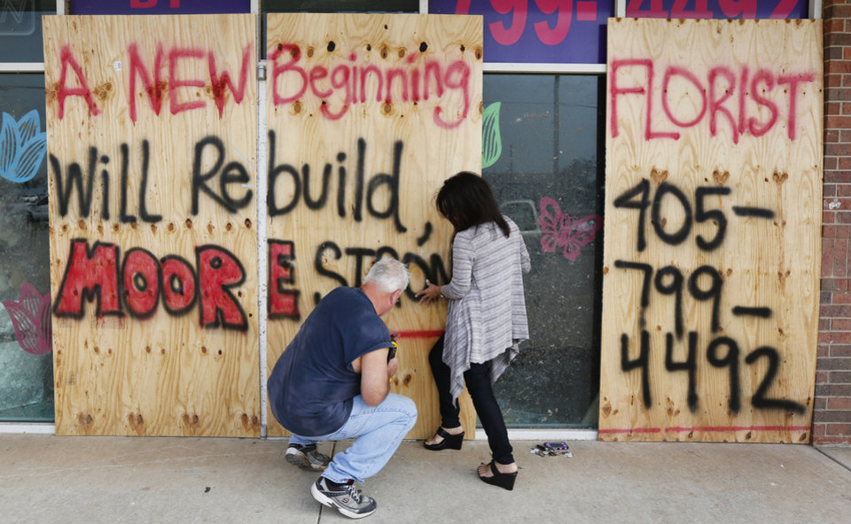 Doug Juergens and Lu Zapp put boards up on A New Beginning Florist in Moore, Friday May 24, 2013. The flower shop is located at SW 4th and Telephone Road and was damaged by a massive tornado that hit Monday. Photo By Steve Gooch, The Oklahoman