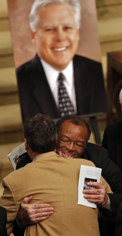 Photo - Dewey Selmon hug a mourner during the funeral services  for former University of Oklahoma football player Steve Davis at the First Baptist Church on Monday, March 25, 2013, in Tulsa, Okla. Davis died in a plane crash last week in Indiana. Photo by Chris Landsberger, The Oklahoman