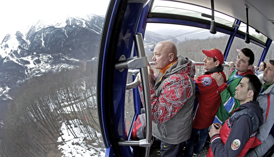 Photo - Fans watch the view from a gondola as the head to a cross-country sprint race at the 2014 Winter Olympics, Tuesday, Feb. 11, 2014, in Krasnaya Polyana, Russia. (AP Photo/Charlie Riedel)