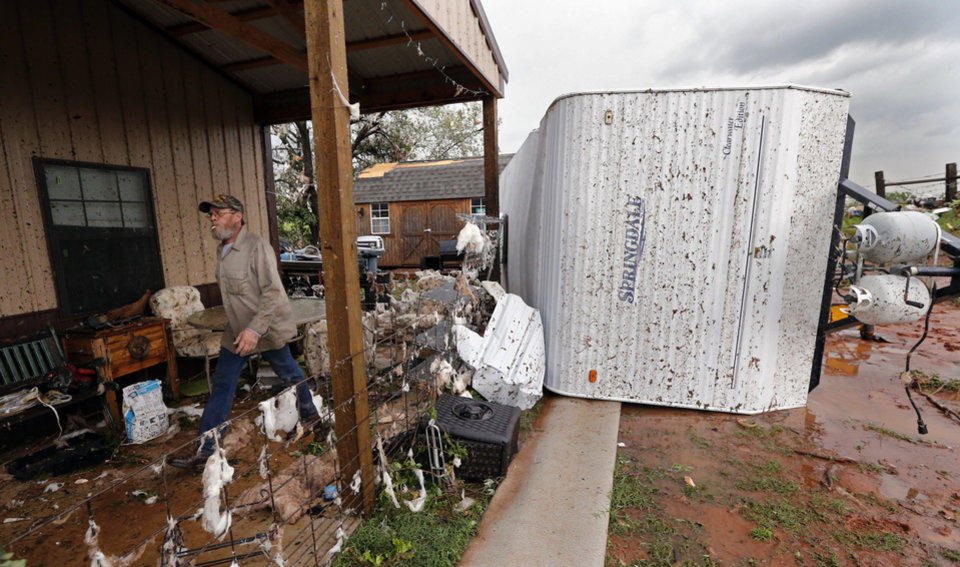 Photo - Buck Wall walks past debris and an overturned travel trailer as residents sort through debris for valuables after a tornado ripped through Bridge Creek, Okla. on Wednesday, May 6, 2015.  Photo by Steve Sisney, The Oklahoman