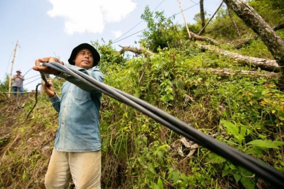 Photo -  Local villagers were instrumental in helping the linemen with nontechnical tasks to successfully complete the project, officials say.
