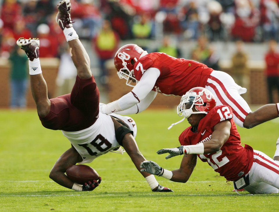 Photo - Oklahoma's Corey Nelson (7) and the player wearing number 12 combine to bring down Nehemiah Hicks (81) during the first half of the college football game between the Texas A&M Aggies and the University of Oklahoma Sooners (OU) at Gaylord Family-Oklahoma Memorial Stadium on Saturday, Nov. 5, 2011, in Norman, Okla. Photo by Steve Sisney, The Oklahoman