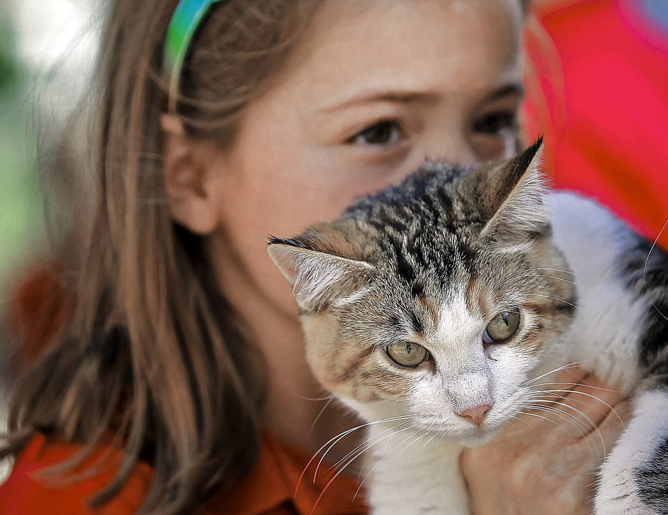 Photo - Laurel Kelley snuggles up to her cat, Coco, during the blessing of the animals at St. Elizabeth Ann Seton Catholic School.   Photo by Chris Landsberger, The Oklahoman  CHRIS LANDSBERGER - CHRIS LANDSBERGER
