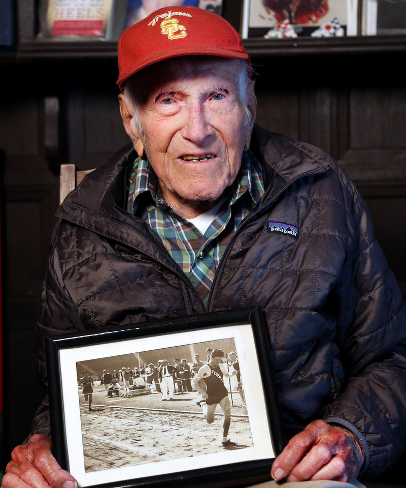 Photo - This Jan. 21, 2014 photo provided by USC Dornsife College of Letters, Arts and Sciences, Louis Zamperini displays one of his photographs as a student and sprinter, at his Los Angeles home. Zamperini, a U.S. Olympic distance runner and World War II veteran who survived 47 days on a raft in the Pacific after his bomber crashed, then endured two years in Japanese prison camps, died Wednesday, July 2, 2014, according to Universal Pictures studio spokesman Michael Moses. He was 97.  (AP Photo/Matt Meindl/USC Dornsife College of Letters, Arts and Sciences)
