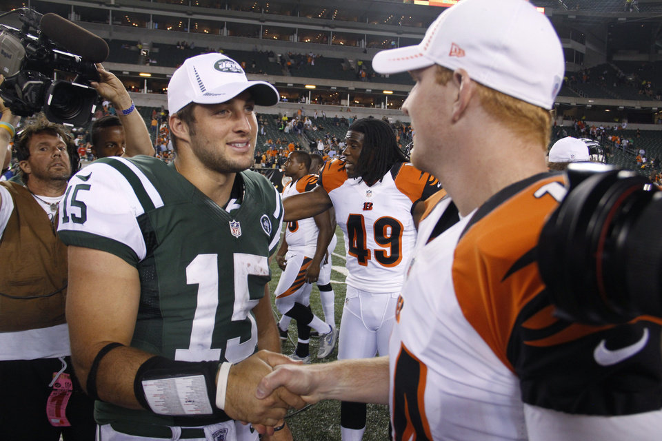 Photo -   New York Jets quarterback Tim Tebow (15) meets with Cincinnati Bengals quarterback Andy Dalton after an NFL preseason football game, Friday, Aug. 10, 2012, in Cincinnati. The Bengals won 17-6. (AP Photo/Tom Uhlman)