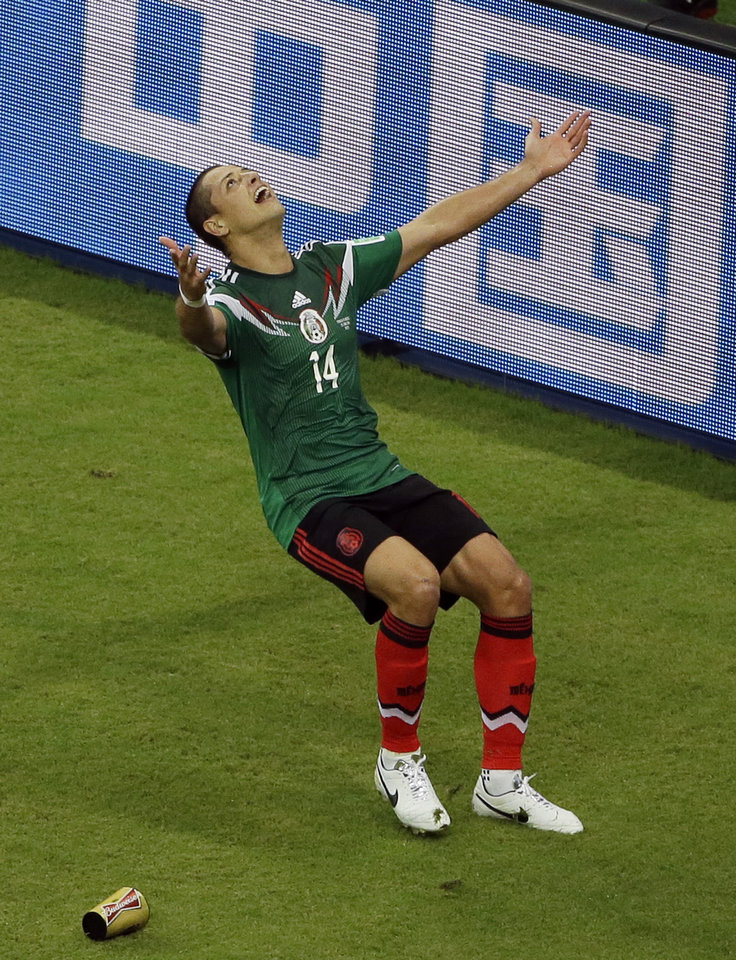 Photo - Mexico's Javier Hernandez (14) celebrates scoring his side's 3rd goal during the group A World Cup soccer match between Croatia and Mexico at the Arena Pernambuco in Recife, Brazil, Monday, June 23, 2014. (AP Photo/Hassan Ammar)