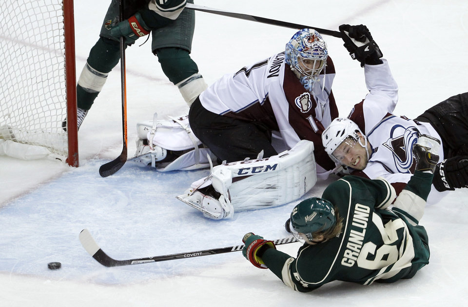 Photo - Minnesota Wild center Mikael Granlund (64), of Finland, shoots the puck around Colorado Avalanche defenseman Erik Johnson (6) and  Avalanche goalie Semyon Varlamov (1), of Russia, to score the game-winning goal during overtime of Game 3 of an NHL hockey first-round playoff series in St. Paul, Minn., Monday, April 21, 2014. The Wild won 1-0 in overtime. (AP Photo/Ann Heisenfelt)
