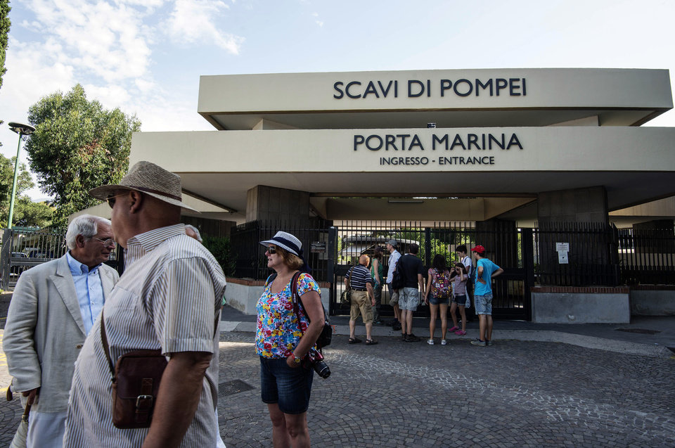 Photo - People wait in front of Pompeii main gate, Italy, Monday, June 23, 2014. A labor dispute kept tourists locked out of Pompeii for part of Monday, the latest in a spate of hours-long closures at the ancient Roman ruins. The gates were unlocked a couple of hours late, frustrating tourists wanting to enter the sprawling ruins in early morning. The dispute over work schedules and back pay began last week, keeping thousands of visitors shut out for hours at a time during union meetings. The government office that runs Pompeii said that three assemblies planned later this week were canceled, meaning visitors could expect regular opening hours. (AP Photo/Salvatore Laporta)