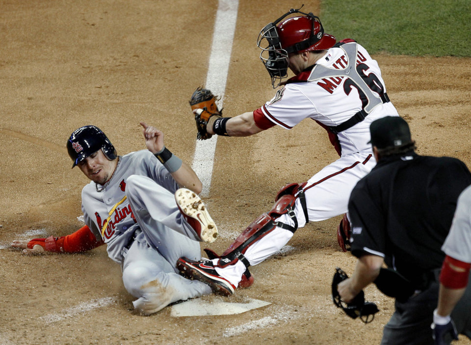 Photo -   St. Louis Cardinals' Tyler Greene scores against Arizona Diamondbacks catcher Miguel Montero during the fourth inning of a baseball game Monday, May 7, 2012, in Phoenix. (AP Photo/Matt York)