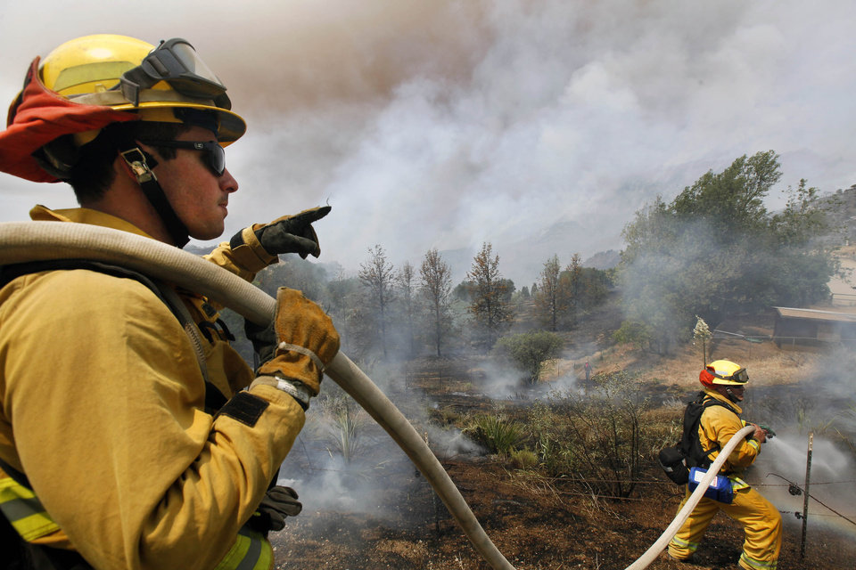 Firefighters from Riverside, Calif. work to extinguish a brush fire at Point Mugu, Calif.,  Friday, May 3, 2013. A Southern California wildfire carving a path to the sea grew to more than 15 square miles and crews prepared Friday for another bad day of gusting winds and searing weather. (AP Photo/Nick Ut) ORG XMIT: LA111