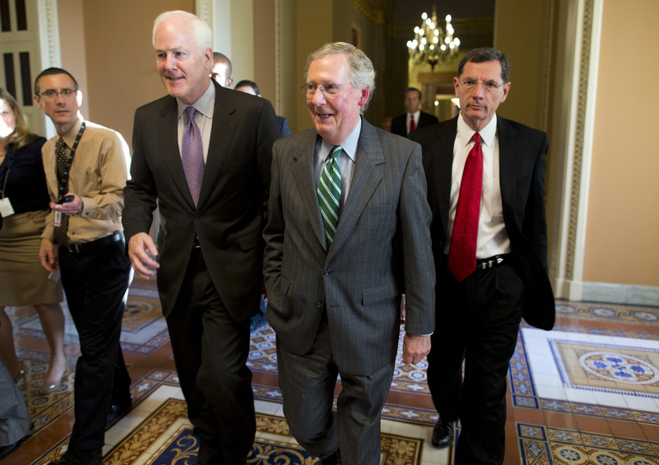 Photo - Senate Minority Leader Sen. Mitch McConnell, R-Ky., center, walks with Sen. John Cornyn, R-Texas, left, and Sen. John Barrasso, R-Wyo., to the Senate floor on Capitol Hill on Monday, Oct. 14, 2013 in Washington. The federal government remains partially shut down and faces a first-ever default between Oct. 17 and the end of the month. (AP Photo/ Evan Vucci)