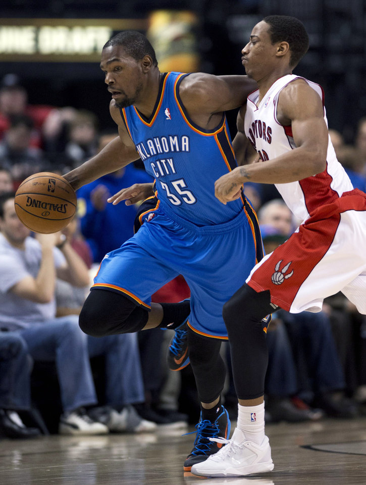 Photo - Toronto Raptors guard DeMar DeRozan, right, tries to strip the ball from Oklahoma City Thunder forward Kevin Durant (35) during the first half of NBA basketball game action in Toronto on Sunday, Jan. 6, 2013. (AP Photo/The Canadian Press, Frank Gunn)  ORG XMIT: FNG102