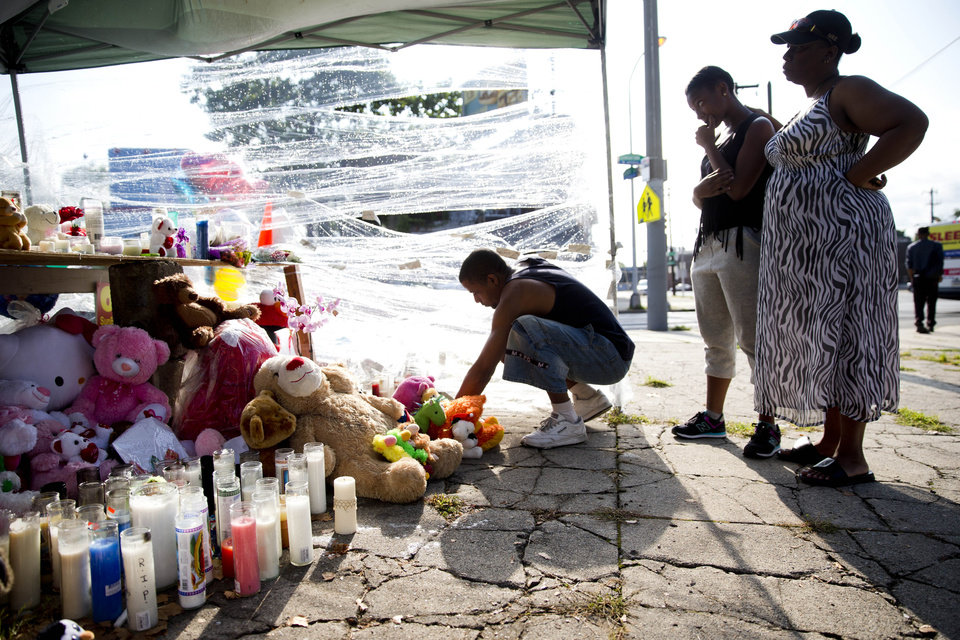 Photo - Richard Starchia, left, Riconya Jackson, center, and her mother Tonia Jackson pay their respects Monday, July 28, 2014, at a makeshift memorial for three children who were killed by a hijacked car that lost control Friday and hit a group of people, in Philadelphia. Police investigators are talking to two people in connection with the search for two carjackers who rammed a stolen sport utility vehicle into a family in north Philadelphia, killing three children. (AP Photo/Matt Rourke)