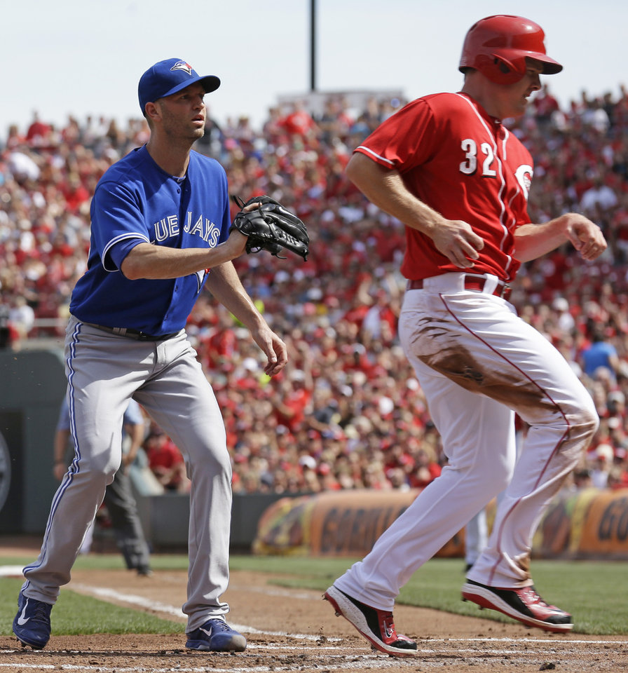 Photo - Cincinnati Reds' Jay Bruce (32) scores past Toronto Blue Jays starting pitcher J.A. Happ on a passed ball by catcher Erik Kratz in the first inning of a baseball game, Saturday, June 21, 2014, in Cincinnati. (AP Photo/Al Behrman)