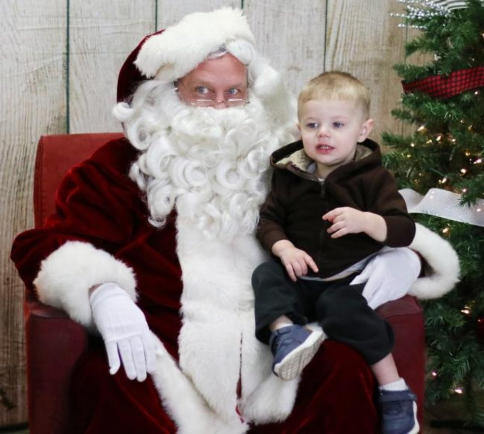 Photo -  Isaiah Werner, 2, sits on Santa's lap during the