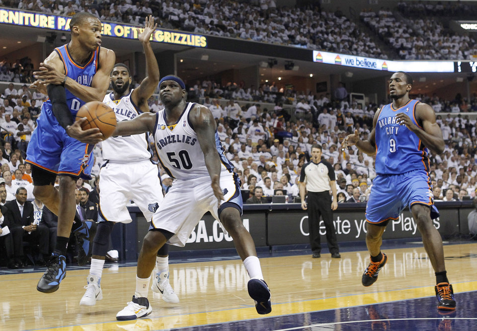 Oklahoma City Thunder guard Russell Westbrook (0) passes to Serge Ibaka (9) as Westbrook is defended by Memphis Grizzlies forward Zach Randolph (50) and O. J. Mayo, second from left, during the first half of Game 6 of a second-round NBA basketball playoff series on Friday, May 13, 2011, in Memphis, Tenn. (AP Photo/Lance Murphey)