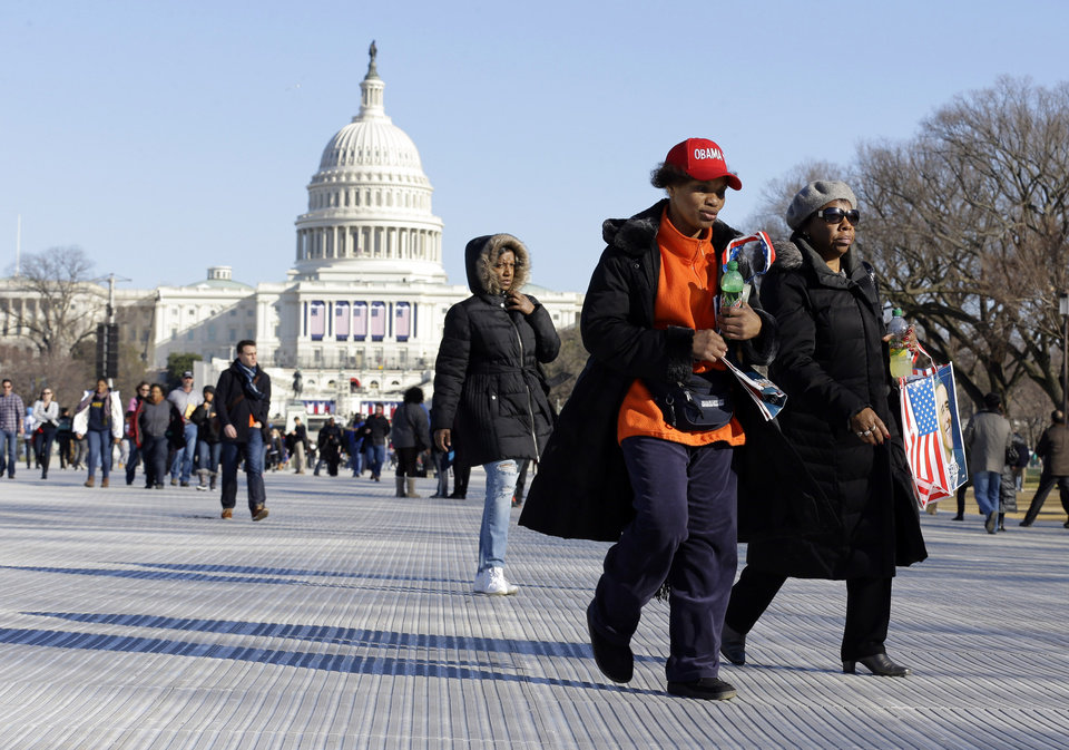 Barbara Whittaker, center, and Fran Willis, right, both of Richton Park, Ill., walk on the National Mall Sunday, Jan. 20, 2013,with the U.S. Capitol prepared for the ceremonial swearing-in of President Barack Obama, the 57th Presidential Inaugural on Monday in Washington. (AP Photo/Alex Brandon)