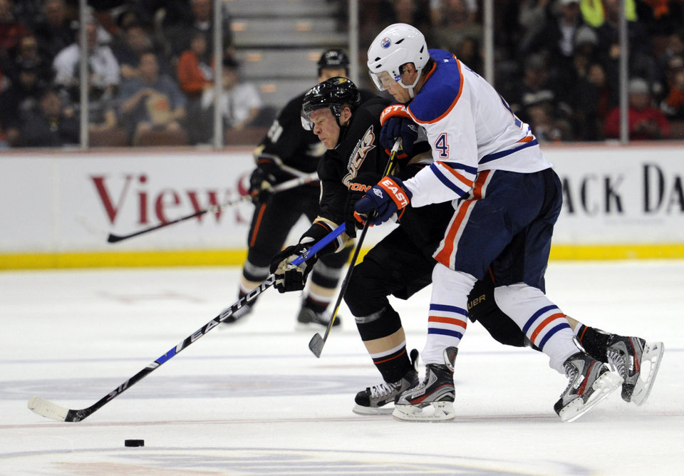 Photo -   Anaheim Ducks right wing Corey Perry, left, keeps the puck away from Edmonton Oilers left wing Taylor Hall (4) in the second period of an NHL hockey game in Anaheim, Calif., Monday, March 5, 2012. (AP Photo/Lori Shepler)