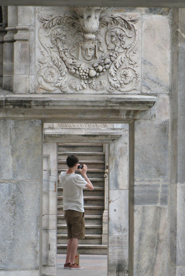 Photo - This July 6, 2012 photo shows a man taking a picture on the rooftop of the Milan cathedral in Milan, Italy. To travel through northern Italy with a copy of Mark Twain's 1869 ''The Innocents Abroad', his classic 'record of a pleasure trip'. It took him to the great sights of Europe and on to Constantinople and Jerusalem before he sailed home to New York. Such a trip would take far too big a chunk out of my holiday time. But, Milan, Florence and Venice, a mere fragment for Twain, was within my reach for a two-week vacation. (AP Photo/Raf Casert)