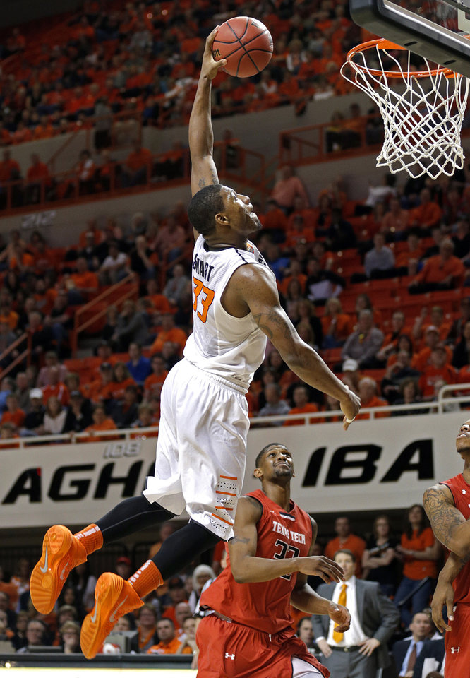 Photo - Oklahoma State's Marcus Smart (33) goes up for a dunk in front of Jordan Tolbert (32) during the men's college basketball game between Oklahoma State and Texas Tech at Gallagher-Iba Arena in Stillwater, Okla., Saturday, Feb. 22, 2014. OSU won 84-62. 