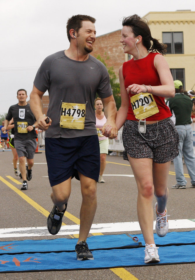 Brad and Katie Mehl, of Edmond, hold hands as they cross the finish line at the Oklahoma City Memorial Marathon Sunday, April 26, 2009. Photo by Doug Hoke, The Oklahoman.