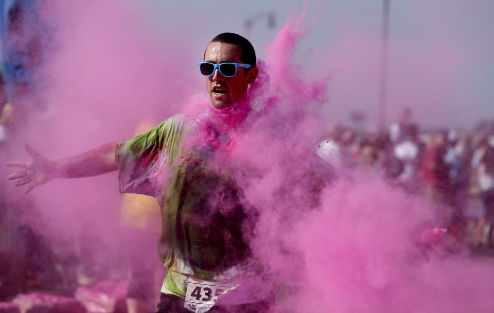 Photo - A competitor finishes the Color Me Rad 5K at the State Fair Park in Oklahoma City, Saturday, July 14, 2012. The race helped raised money for the Cystic Fibrosis Foundation. Photo by Sarah Phipps, The Oklahoman.