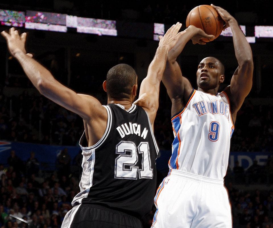 Oklahoma City's Serge Ibaka (9) shoots against San Antonio's Tim Duncan (21) during an NBA basketball game between the Oklahoma City Thunder and the San Antonio Spurs in Oklahoma City Monday, Dec. 17, 2012. Oklahoma City won, 107-93. Photo by Nate Billings, The Oklahoman