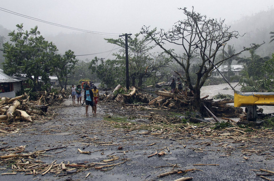 Photo - People walk through debris in Samoa's capital Apia, Friday, Dec. 14, 2012, after cyclone Evan ripped through the South Pacific island nation.  The powerful cyclone flattened homes and uprooted trees with winds of up to 165 kilometers (100 miles) per hour. Phone lines, Internet service and electricity were down across the country, and the airport was closed. (AP Photo/Seti Afoa)