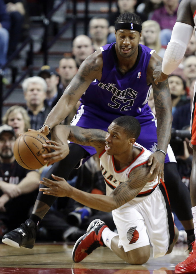 Portland Trail Blazers guard Damian Lillard, bottom, passes off as Sacramento Kings forward James Johnson defends during the first quarter of an NBA basketball game in Portland, Ore., Wednesday, Dec. 26, 2012. (AP Photo/Don Ryan)