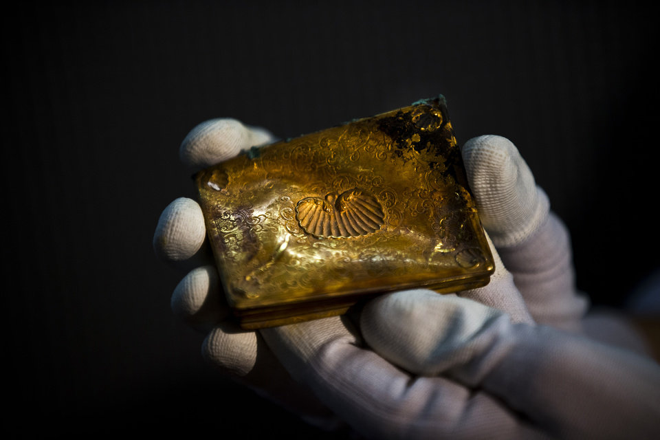 Photo - A worker of the ministry holds up  for photographers a gold tobacco box from the shipwreck of a 1804 galleon, on its first display to the media at a Ministry building, in Madrid, Friday, Nov. 30, 2012. Spanish cultural officials have allowed the first peep at 16 tons (14.5 metric tons) of the shipwreck, 'Nuestra Senora de las Mercedes' a treasure worth an estimated $500 million that a U.S. salvage company gave up after a five-year international ownership dispute. (AP Photo/Daniel Ochoa de Olza)