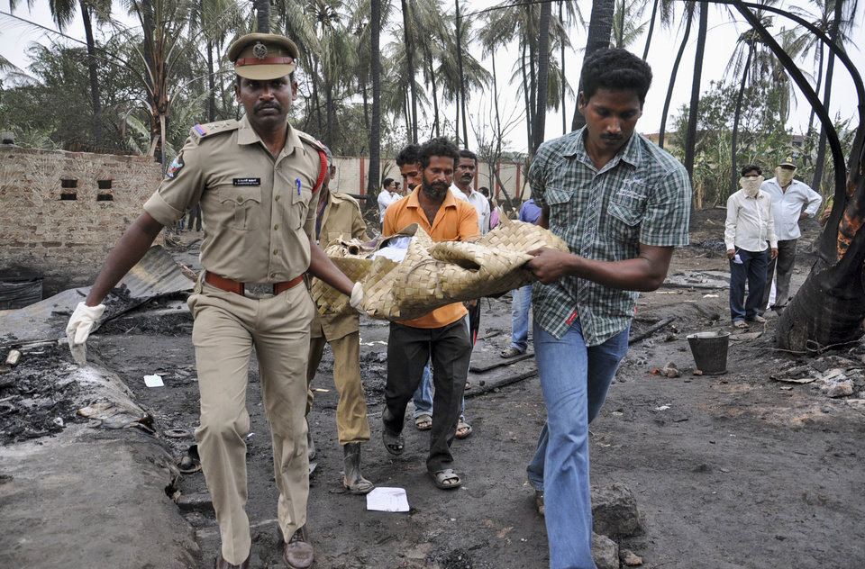 Photo - Indian police officers and rescue workers carry the body of a pipeline blast victim in Nagaram village, India, Friday, June 27, 2014. A state-owned gas pipeline exploded and burst into flames Friday, killing at least 15 people, destroying homes and forcing the evacuation of neighboring villages in the southern Indian state of Andhra Pradesh, authorities said. (AP Photo)