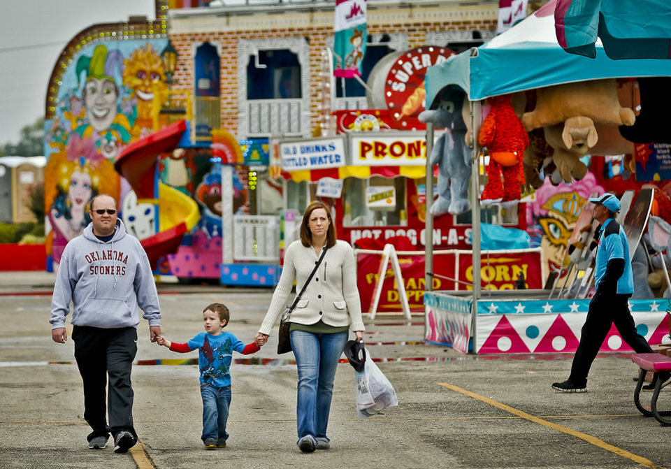 Photo - Brandon Downing with his son Wyatt and wife Katy check out the sights as they walk the midway at the Oklahoma State Fair at State Fair Park on Friday, Sept. 14, 2012, in Oklahoma City, Oklahoma.  Photo by Chris Landsberger, The Oklahoman