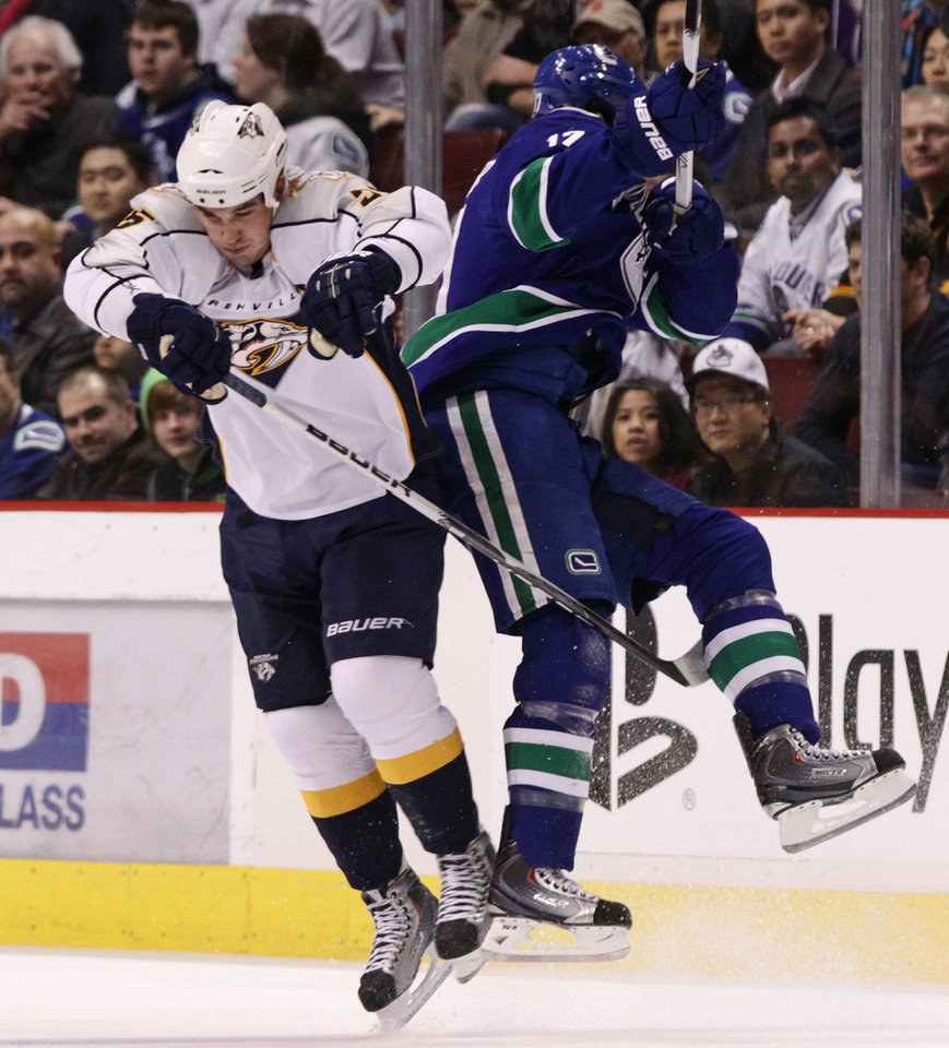 Nashville Predators' Shane O'Brien, left, and Vancouver Canucks' Ryan Kesler collide during the first period of an NHL hockey game in Vancouver, British Columbia, on Wednesday, Jan. 26, 2011. (AP Photo/The Canadian Press, Darryl Dyck)