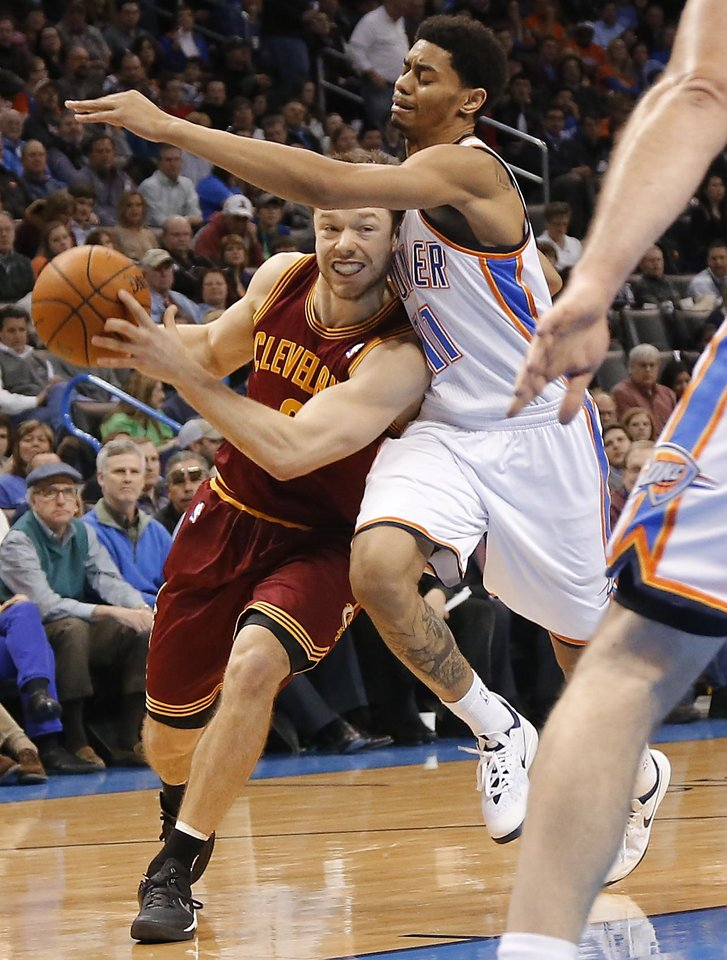 Photo - Cleveland's Matthew Dellavedova (8) drives past Oklahoma City's Jeremy Lamb (11) during the NBA basketball game between the Oklahoma City Thunder and the Cleveland Cavaliers at the Chesapeake Energy Arena in Oklahoma City, Okla. on Wednesday, Feb. 26, 2014.  Photo by Chris Landsberger, The Oklahoman