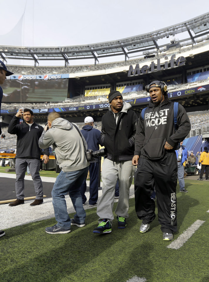 Photo - Seattle Seahawks quarterback Russell Wilson, left, and running back Marshawn Lynch, right, make a brief visit to MetLife Stadium along with other members of the team Saturday, Feb. 1, 2014, in East Rutherford, N.J. The Seahawks and the Denver Broncos are scheduled to play in the Super Bowl XLVIII football game Sunday, Feb. 2, 2014. (AP Photo/Jeff Roberson)